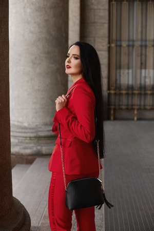 Young businesswoman with red lips and in the red stylish suit posing outdoors on the city street