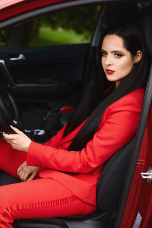 Side view of a model girl in a red suit sitting in the red car and keeping hands on the wheel