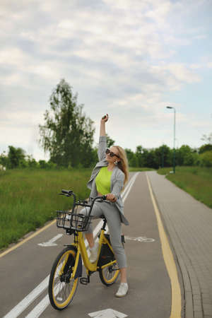 Young model girl in summer outfit posing outdoors with vintage yellow bicycle, smiling and have fun
