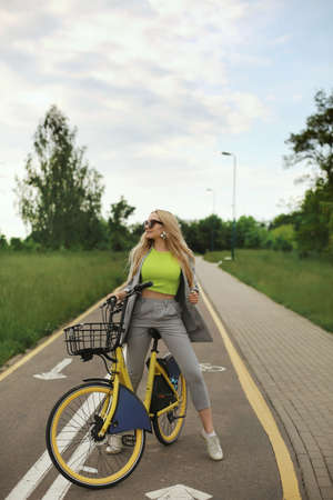 Young beautiful hipster woman in a light green top posing with yellow bicycle outdoors on the summer day 免版税图像
