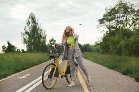 Young model girl in modish clothes posing with yellow bicycle at the bike path 免版税图像