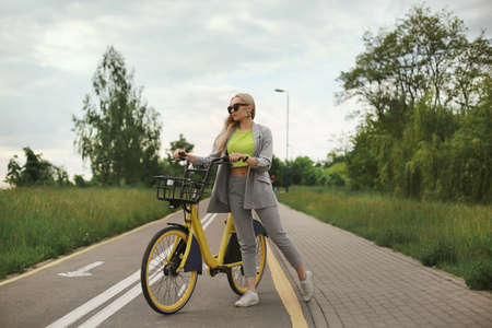 A young woman in trendy hipster outfit posing alone with yellow bicycle at the bike path