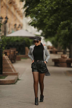 Autumn portrait of the model girl in sunglasses, leather shorts and trendy trench coat walking on the city street