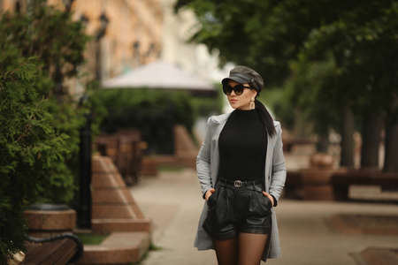 A young woman wearing an autumn outfit walking by the sidewalk in the European city 免版税图像