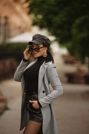 Adult fashionable model in a trendy trench coat, leather shorts and hat looking in the camera and posing outdoors 免版税图像