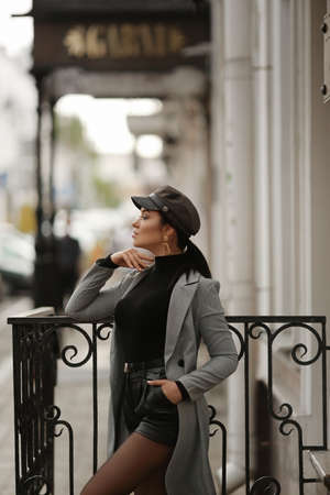 Side view of a model girl in modish autumn clothes stands on the European city street, looking aside and waiting for something
