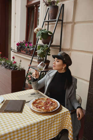 Model girl in fashionable clothes sitting outdoors at the cafe table, drinking wine and eating pizza