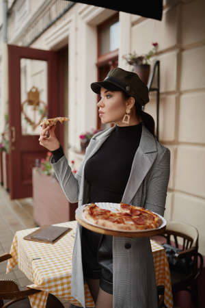 Adult model girl in trendy clothes holding a tasty pizza and posing outdoors on an autumn day
