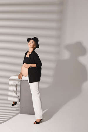 A young pregnant model in a trendy outfit posing in a white studio with shadows in the background
