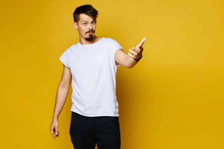 Surprised emotional young man with mustache and small beard in white blank t-shirt posing over yellow background, studio portrait with copy space. Peoples emotions lifestyle concept