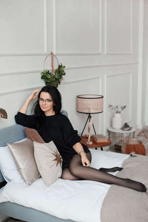 Young woman with dark hair in black dress and round stylish glasses posing on the bed in a luxury minimalist interior
