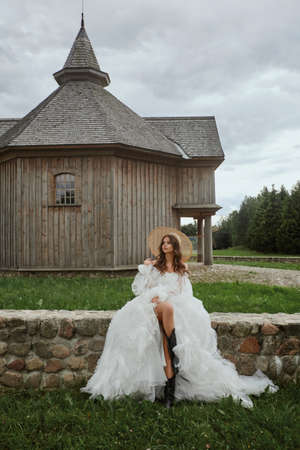 Beautiful leggy model girl in a wedding dress and straw hat posing near the wooden church in the countryside. Young woman bride in a modish vintage dress. Concept of wedding fashion