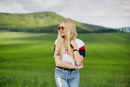 Cute blonde model in pink sunglasses smiling and posing outdoors with the beautiful landscape in the background