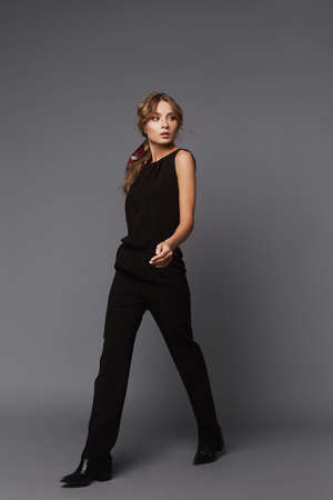 A young woman in a black casual outfit walking over the grey background. Model girl in a black suit on the grey background