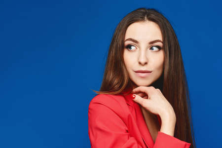 Portrait of the young model woman with perfect nude makeup in a red suit against the blue background