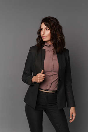 Middle-aged businesswoman dressed in a dark suit and pink silk blouse against the grey background, concept of business clothes for meetings and walks 免版税图像