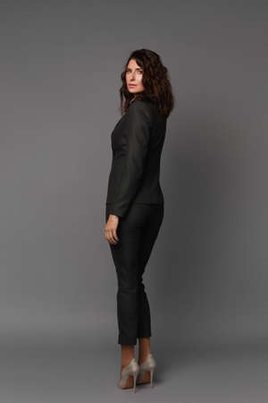 Full-length portrait of an adult model woman with perfect body wearing a dark suit and high-heeled shoes posing against grey background, concept of business clothes for meetings and walks