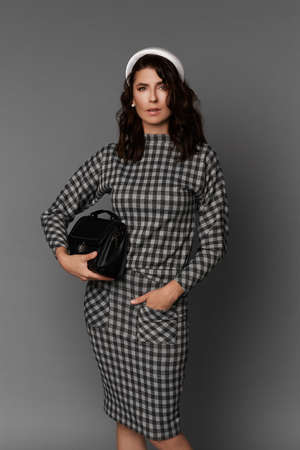 Beautiful adult woman with gentle makeup wearing checkered dress holding black purse and posing against a grey background