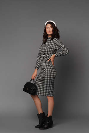 Middle-aged model woman with a great figure wearing a checkered dress on the grey background 免版税图像