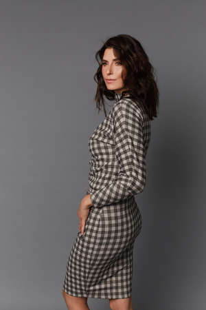 Beautiful adult woman with perfect makeup wearing a checkered dress on the grey background