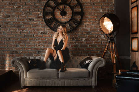 Fashion portrait of a young beautiful female model in casual black dress and black boots sits on the vintage sofa