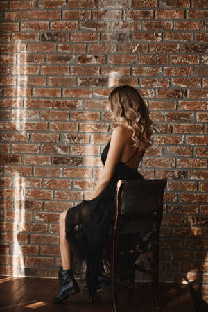 Side view of a young model woman in a black dress and black boots sits on the stool against the brick wall 免版税图像