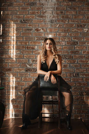 Fashion portrait of a female model with perfect evening makeup wearing a black dress and black boots against the brick wall indoors