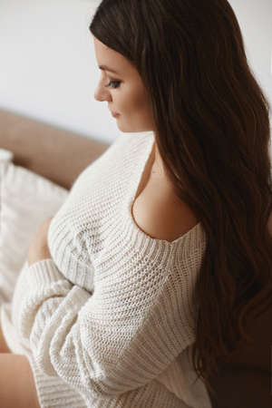 Beautiful young pregnant woman with dark hair wearing white knitted dress posing on the sofa