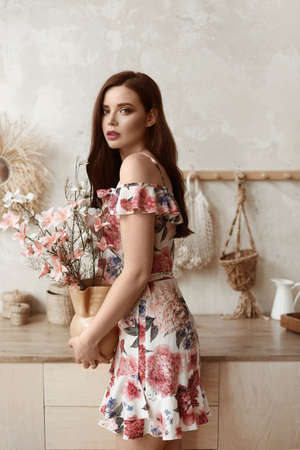 Young woman with full lips and perfect makeup in short summer dress keeps vase with flowers in the kitchen interior