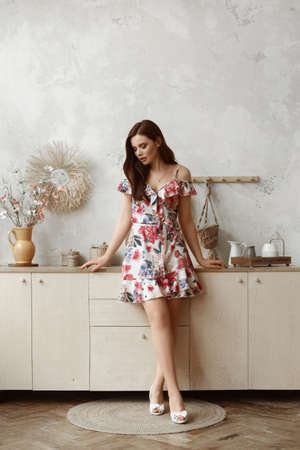 Beautiful female model in short summer dress stands at the kitchen in a cozy interior 免版税图像