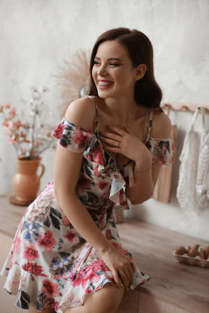 Happy young woman in a short dress with flower print posing at the kitchen interior in the morning 免版税图像