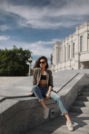 Young model woman in trendy sunglasses, jeans, and fashionable jacket posing outdoors in a European city in the summer day