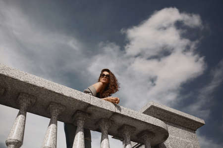 Fashion outdoor shoot of a beautiful female model in trendy sunglasses with blue sky behind