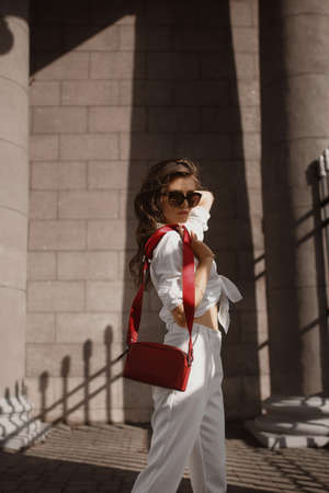Young female model with perfect slim body in trendy sunglasses and white pants and shirt walking on the sidewalk of the European city