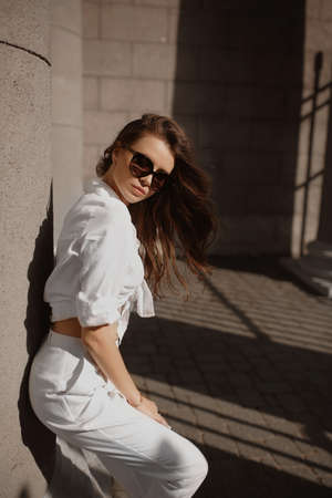 Young female model with perfect slim body in trendy sunglasses and white pants and shirt posing on the street of the European city