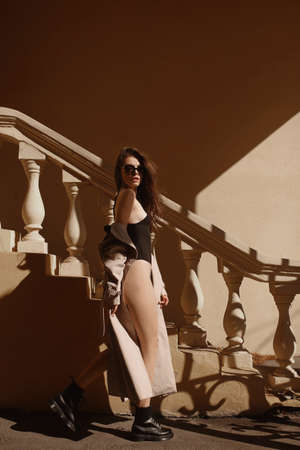 Slim woman with a perfect body in black bodysuit and beige raincoat posing outdoors on the summer sunny day