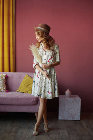 Young woman with slim figure in beige hat and sundress posing in pink interior