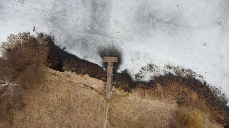 Top view of a wooden pier on the frozen lake in the early spring 免版税图像