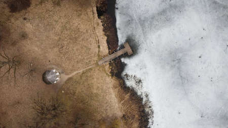 Aerial view of the wooden pier on the frozen lake on a spring day 免版税图像