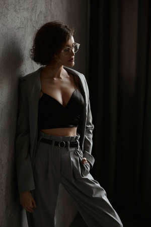 Young woman with great body in black cami top and trendy grey suit posing indoors