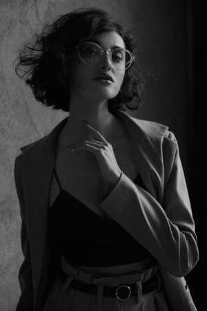 High fashioned portrait of the female model wearing eyeglasses in a black satin cami top, black and white photography 免版税图像