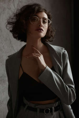 High fashioned portrait of the female model wearing eyeglasses in a black satin cami top