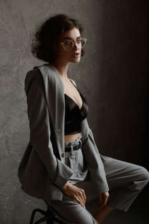 High fashion female model in a black cami top and grey pants on grey background. Studio shoot