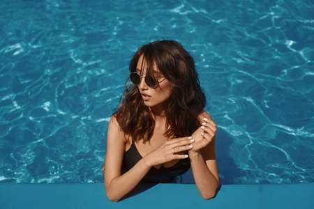 A young model woman in a black swimsuit and trendy sunglasses posing in the swimming pool on a summer sunny day