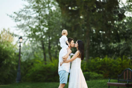 Happy young family, a beautiful young woman with a handsome man and adorable toddler boy, young mother her husband and their little son, posing at a city park on a warm summer day 免版税图像