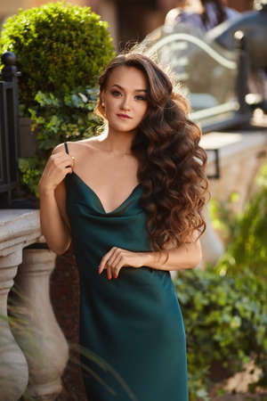 Model girl with perfect makeup in a trendy summer dress posing outdoor on the summer sunny day
