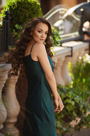 Model girl with slim perfect body in trendy dress posing outdoors on the summer day