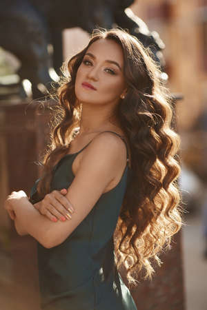 Young woman with perfect makeup and wavy long hair in satin dress posing outdoor