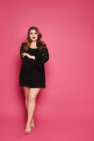 A beautiful young plump woman with makeup in pin-up style wearing black short dress posing against a pink background 免版税图像