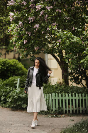 Pretty model girl in summer midi skirt and leather jacket posing near a bloomy tree. Young brunette woman in spring outfit posing outdoors 免版税图像